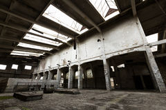 Abandon industrial interior. A desolate old industrial building inside, pillars Stock Photography
