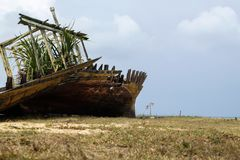 Abandon shipwreck near the sea shore under blue sky background a. Nd bright sun Royalty Free Stock Image