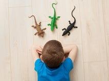 Abandon - un petit garçon triste s'étendant sur le plancher Image stock