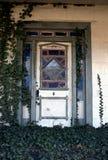 Abandonado a casa con la hiedra que crece en el pórtico Foto de archivo