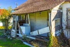 Abandonado a casa con la lavadora en el pórtico Foto de archivo libre de regalías