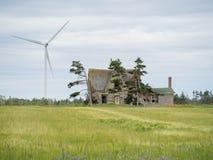 Abandonado a casa y molino de viento Fotos de archivo libres de regalías