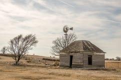 Abandonado a casa y molino de viento Foto de archivo libre de regalías