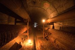 Abandonado em volta do túnel subterrâneo do concreto do cano principal de aquecimento com tubos oxidados imagem de stock