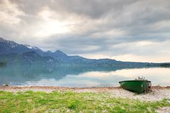 Abandonado pescando el barco de paleta en el banco del lago alps Lago morning que brilla intensamente por luz del sol Imagenes de archivo