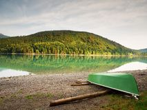 Abandonado pescando el barco de paleta en el banco del lago alps Lago morning que brilla intensamente por luz del sol Imagen de archivo libre de regalías