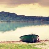 Abandonado pescando el barco de paleta en el banco Lago alps de la mañana Imágenes de archivo libres de regalías