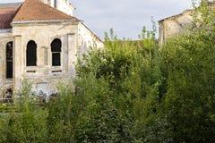 Abandonado y crecido demasiado con las casas de los arbustos Imagenes de archivo