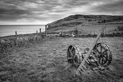 Abandond Farm Equipment. A vintage piece of farm equipment rusting in a field in Ireland. This picture was taken along the Antrim Coast in Northern Ireland. it stock images