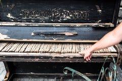 Abandond piano. And hand playing melody Royalty Free Stock Photos