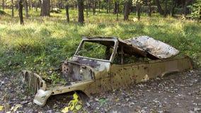 Abandonded bil i trän Arkivfoto