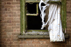 Abandonded building window and curtains. Broken window and abandoned building with curtains blowing in the wind Stock Photography