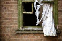 Abandonded byggnadsfönster och gardiner Arkivbild