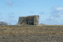 An Abandonded Corn Crib in a Field. A corn crib or corncrib is a type of granary used to dry and store corn. It may also be known as a cornhouse or corn house Royalty Free Stock Photography
