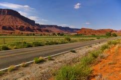 Abandone el camino con tierras de labrantío irrigadas verde y el mesa enorme del rojo en el fondo Fotos de archivo