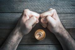 Abandone el concepto de consumición del alcohol con un vidrio de los licores rodeado por 2 puños apretados de mirada subrayados foto de archivo