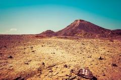 Abandone el paisaje con dos colinas y tierra seca amarilla Ra de Makhtesh Foto de archivo libre de regalías