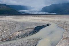 Abandone el paisaje con el río, el glaciar y el cielo tempestuoso, Islandia Fotografía de archivo libre de regalías