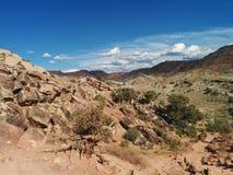 Abandone el paisaje con las rocas grandes en primero plano y montañas Foto de archivo