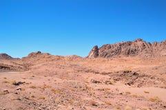 Abandone el paisaje, montañas de la piedra arenisca roja, un llano cubierto con la vegetación rara del desierto, un estiramiento  Foto de archivo