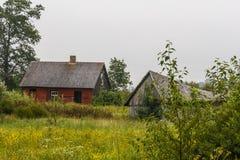 Abandone la casa roja y el granero gris en el país Foto de archivo libre de regalías