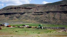 Abandone la granja en un valle con la hierba verde y un acantilado rocoso Fotos de archivo
