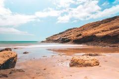 Abandone la playa con las rocas y el cielo azul del claro Foto de archivo libre de regalías