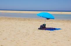 Abandone la playa con las sombras del sol, mar tranquilo, cielo azul, nubes Destino del viaje del verano Imagen de archivo libre de regalías