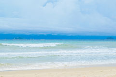 Abandone la playa de la arena con el cielo azul y las ondas Fotografía de archivo