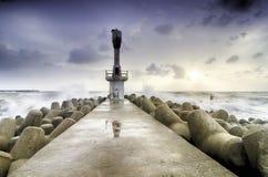 Abandone la torre ligera de faro con agua concreta de la rotura rodeada por la agua de mar sobre fondo de la salida del sol Imagenes de archivo