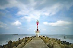 Abandone la torre ligera de faro con agua concreta de la rotura rodeada por la agua de mar en el día soleado Fotos de archivo libres de regalías