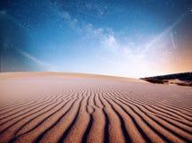 Abandone las dunas de arena en la noche, las estrellas y la vía láctea, astrophoto profundo del cielo Imagen de archivo libre de regalías