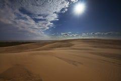 Abandone las dunas de arena, las nubes y el sol brillante Imágenes de archivo libres de regalías