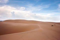 Abandone las dunas del paisaje por la tarde con las nubes del blanco de los cielos azules Imagen de archivo libre de regalías