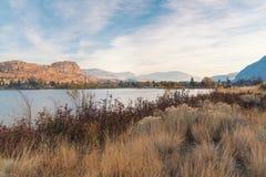 Abandone las hierbas en primero plano con el lago y los acantilados en fondo en la puesta del sol en otoño Imagenes de archivo