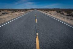 Abandone las líneas amarillas del camino de la carretera y el punto de desaparición Foto de archivo libre de regalías