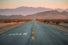 Abandone las líneas amarillas montañas y punto de desaparición del camino de la carretera Fotografía de archivo libre de regalías