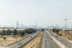 Abandone por otra parte de la carretera principal con los posts de la electricidad y los edificios de la silueta en fondo en Duba Imágenes de archivo libres de regalías