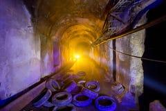 Abandoned översvämmade tunnelen av kabelsamlaren, gamla ruttna gummihjul Arkivfoto