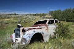 An abandoned 1930's car in a field in Montana. A 1930's style car lies abandoned and detoriating in a filed in Monatana, a relitivley common site in the area Stock Photo