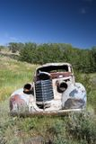 An abandoned 1930's car in a field in Montana. A 1930's style car lies abandoned and detoriating in a filed in Monatana, a relitivley common site in the area Royalty Free Stock Photos