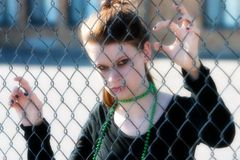Abandoned. Serious teen trapped behind a chain link fence stock photos