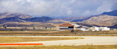 Abandoned Air Field. In Irvine California with beautiful clouds with airport hangar and mountains beyond Royalty Free Stock Photo