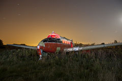 Abandoned airplane at night. Old abandoned airplane in an old airfield at night with star trails Royalty Free Stock Photography