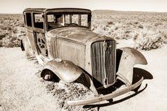 An abandoned antique car near a dessert roadway Stock Photos