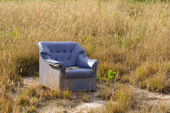 Abandoned armchair out in grass field Royalty Free Stock Photo