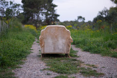 Abandoned armchair. Vintage armchair abandoned in a field Stock Images
