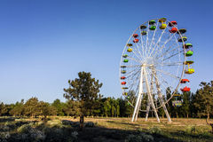 Abandoned attraction - a Ferris wheel with colored cabins in Russian forest. Abandoned attraction - a Ferris wheel merry-go-round with colored cabins in a Royalty Free Stock Image