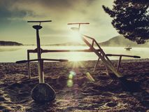 Abandoned baby swing on sandy beach of lake. Cold morning after season in holiday resort. Abandoned baby swing on sandy beach of lake. Cold morning after season stock images