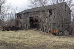 Abandoned Barn. Old dilapidated and abandoned barn with rusty tractors and bare winter trees Royalty Free Stock Photos
